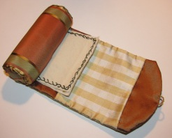 This case is made with a lovely fall toned striped silk on the exterior and a coppery shot silk on the interior. The spacious pocket is a white and golden yellow plaid silk. The two off white wool needle-pages are vine stitched with dark green on the first and golden yellow on the second. The viney stitch is continued on the ends of the cotton batted roll. The case is held closed with a tiny mother of pearl button and loop. This case is entirely hand-sewn and based on an original formerly in my collection and featured in the up-coming  Fanciful Utility. This case took approx. 5 hours to hand-sew.